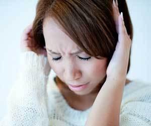 頭を押さえている女性の画像