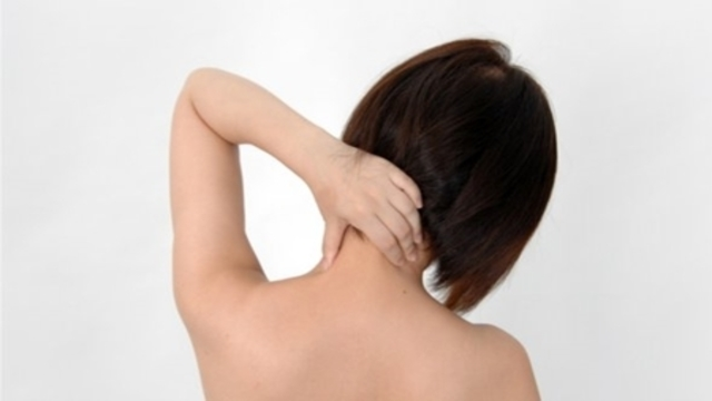 女性が首を押さえている画像