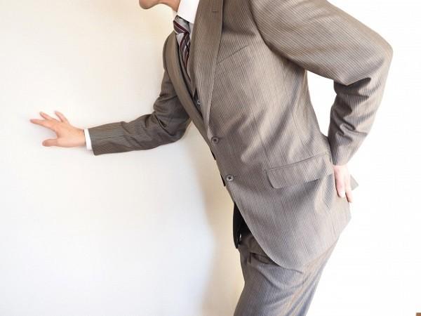 腰を押さえている男性の画像
