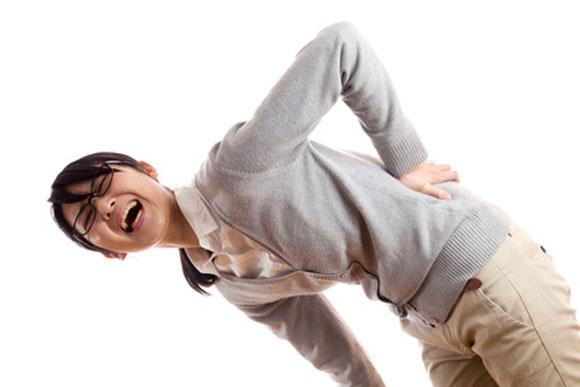 女性が腰を押さえている画像