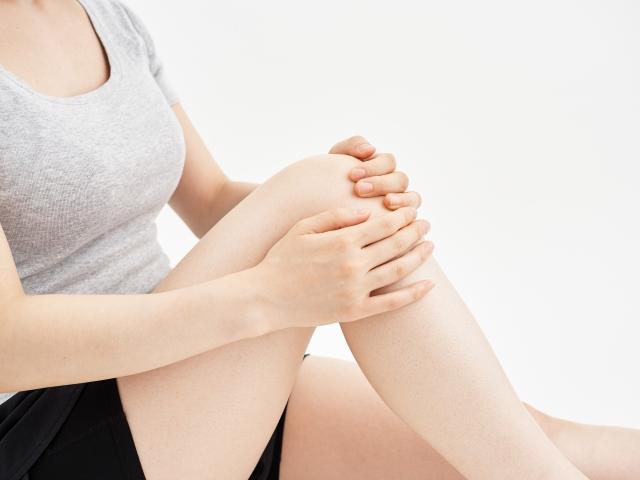 膝を押さえている女性画像
