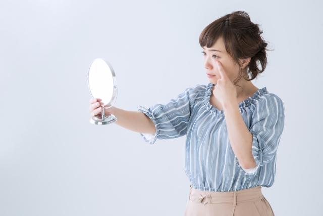 鏡で目を見る女性