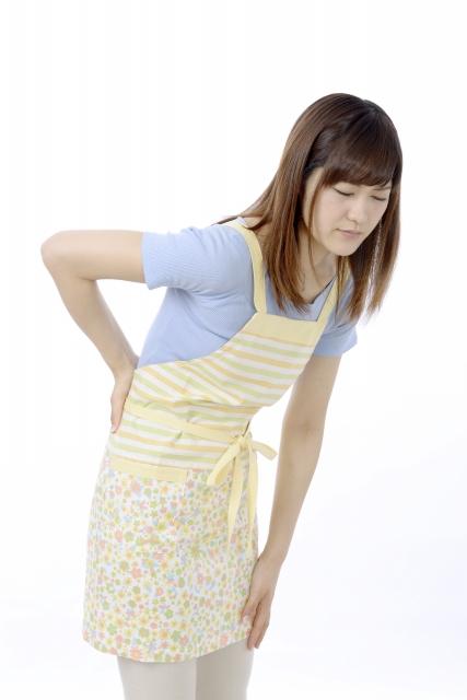 腰(腰椎)を押さえている女性